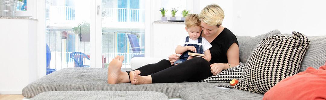 Bild på kvinna som sitter i soffa med ett barn i knät. Titel PMB Sverige bygger för IF och Trygg Hansa.