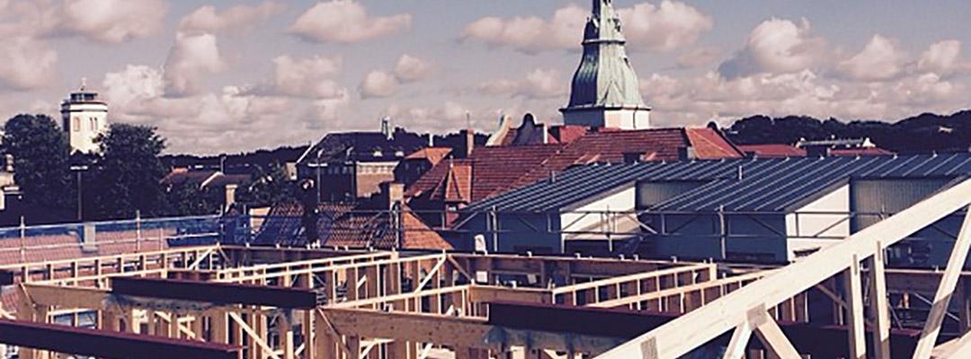 Bild. Bygge med hustak i bakgrunden. Titel PMB Sverige är morgondagens byggentreprenör.